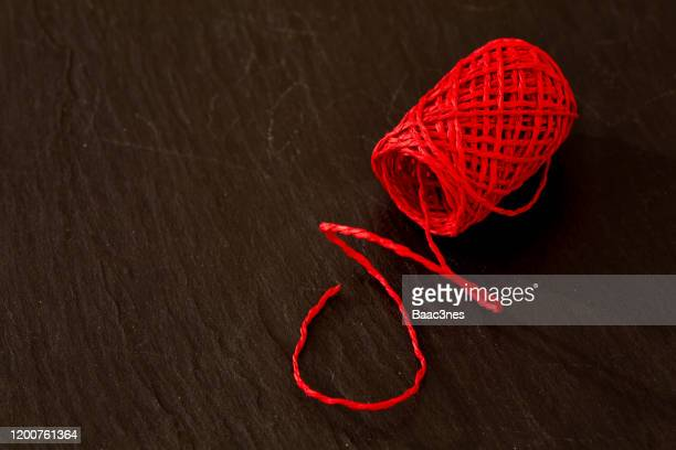 red thread on a rock table - ribbon sewing item stock pictures, royalty-free photos & images