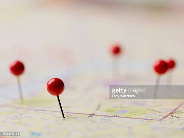 red thumbtacks on map - karte navigationsinstrument stock-fotos und bilder