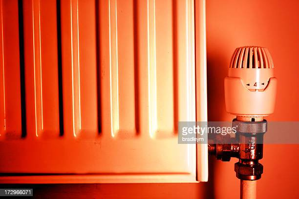 Red tinted photo of a thermostat and radiator