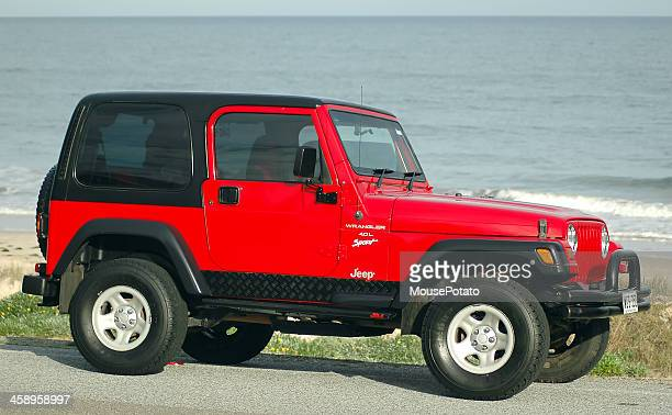 red tj 1997 jeep wrangler hardtop on street at beach - jeep wrangler stock photos and pictures