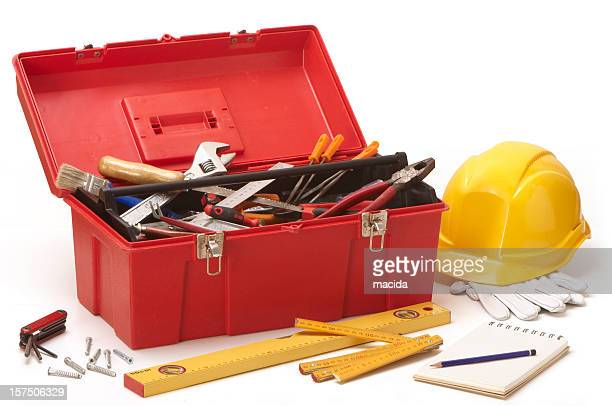 Red tool box filled with tools next to construction hat