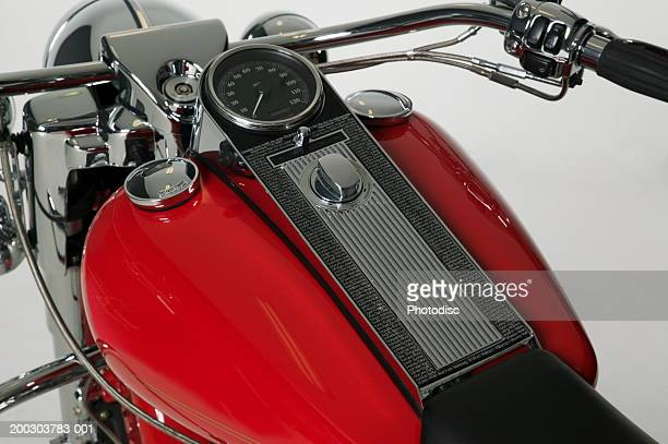 Red touring motorcycle parked in studio, close up of tank