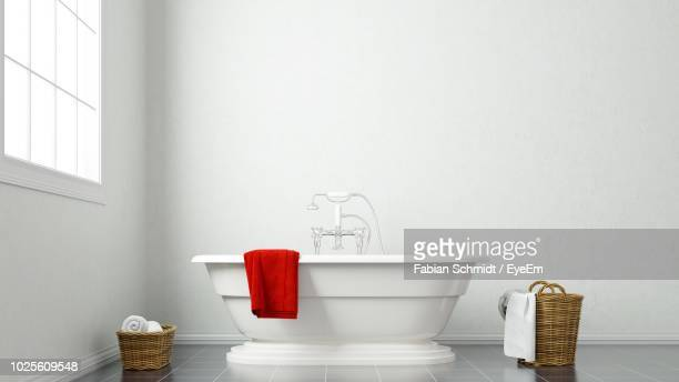 red towel on bathtub against white wall in bathroom - red tub photos et images de collection
