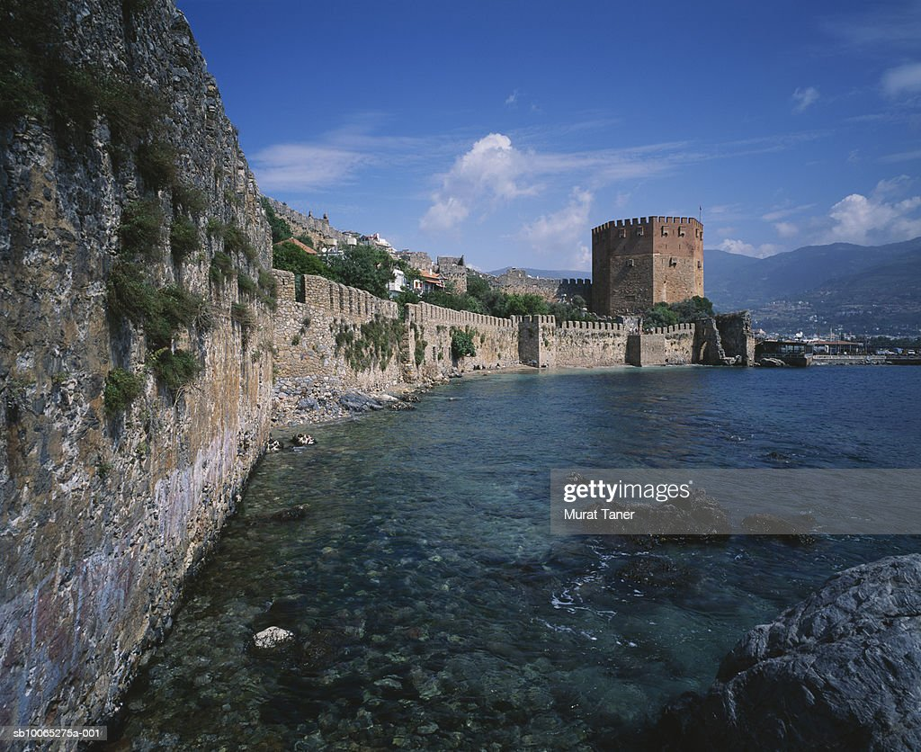 Red tower and castle wall on coastline : Foto stock