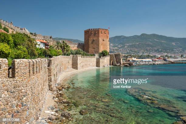 red tower and old walls of the alanya fortress, antalya turkey - antalya province stock pictures, royalty-free photos & images