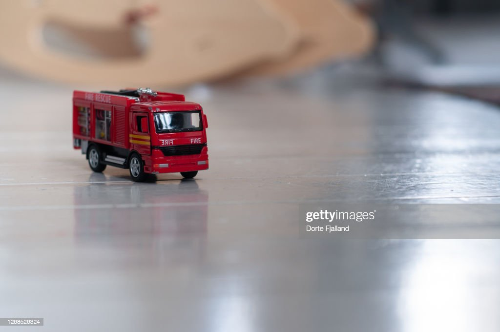 Red toy fire truck on a white wooden floor and blurred background : Foto de stock