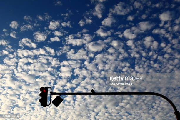 Red traffic light against blue sky with cotton candy clouds