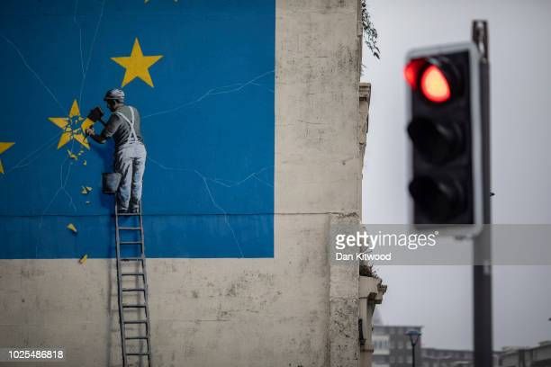 Red traffic light in front of a painted mural by British graffiti artist Banksy, depicting a workman chipping away at one of the stars on a European...
