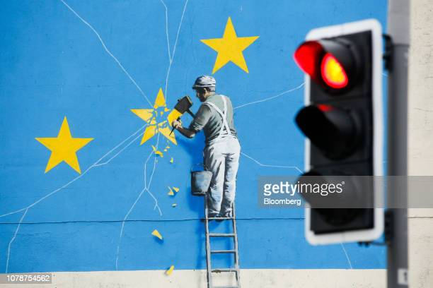 A red traffic light shines in front of a mural by street artist Banksy depicting a European Union flag being chiseled by a workman on the side of a...