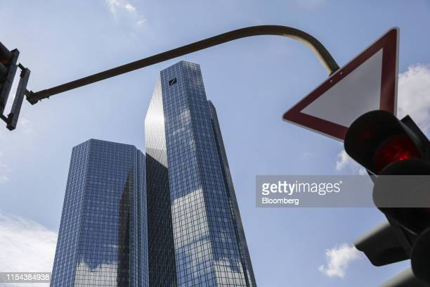 A red traffic light shines in front of the Deutsche Bank AG twin tower headquarters stand in the financial district of Frankfurt Germany on Sunday...