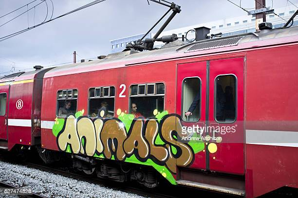 A red train pulled into Brussels train station with 'Animals' graffitied in bubble writing across the side Brussels Belgium