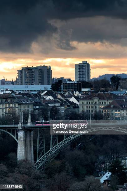 Red tram crosses the bridge with modern buildings in the background. Bern, Canton of Bern, Switzerland, Europe.