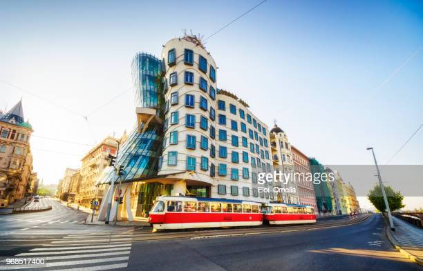 red tram in front of Dancing House (Tančící dům) in the morning. Prague