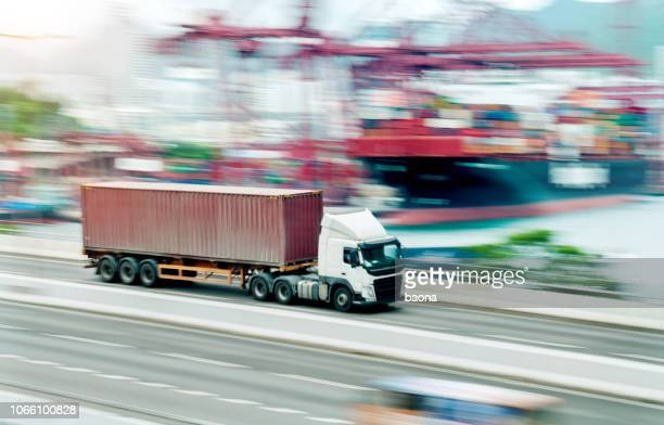 red truck leaving the harbor - box container stock pictures, royalty-free photos & images