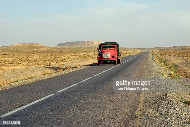 Red truck on a desert road in Morocco