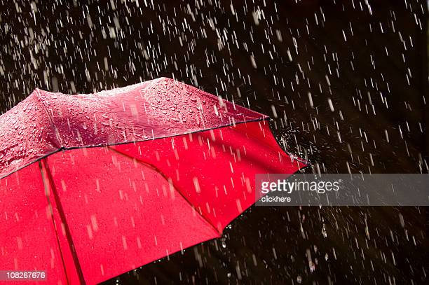 Red Umbrella and Rain Against Black Background