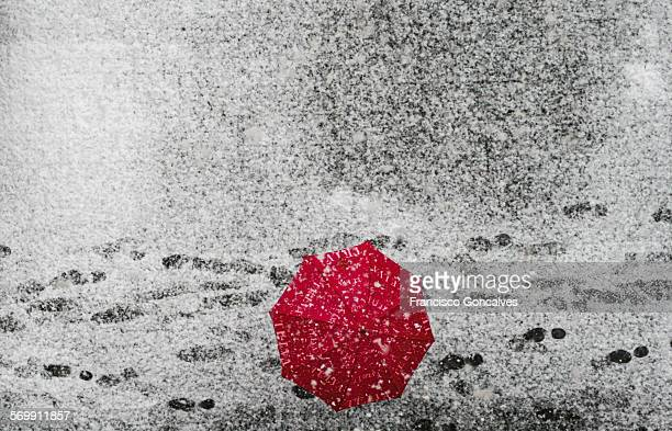 Red umbrella during a snowfall in Barcelona