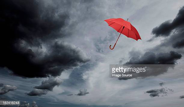 red umbrella floating through cloudy sky - bad luck stock pictures, royalty-free photos & images