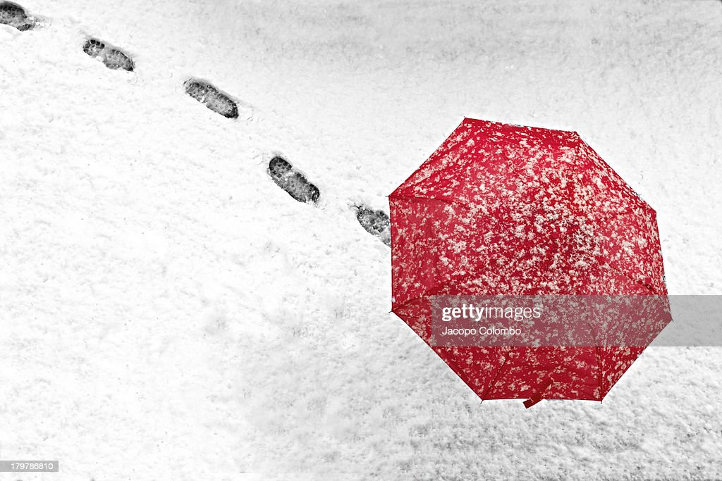 Person walking with a red umbrella in the snow - top view