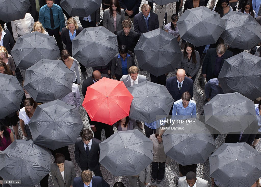 Red umbrella standing out in crowd of business people : Stock Photo