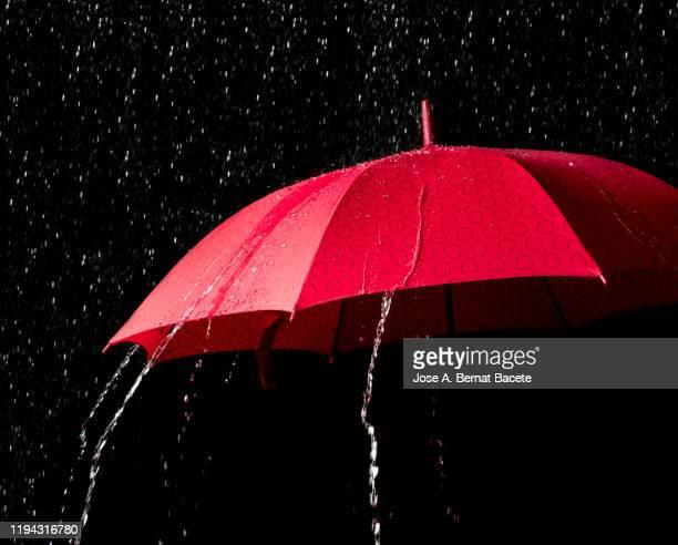 red umbrella with splash on black background. - 傘 ストックフォトと画像