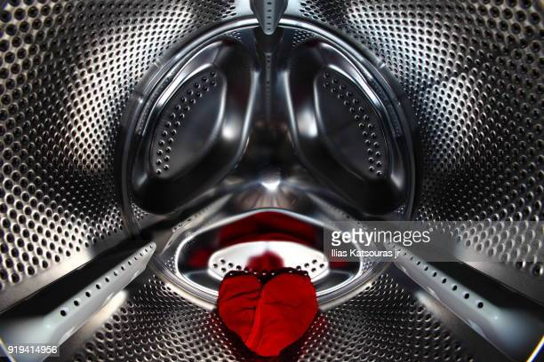 Red underwear in the shape of a heart in washing machine drum, laundry