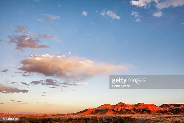a red, utah desert landscape at sunset with sandstone cliff and big sky - robb reece stock-fotos und bilder