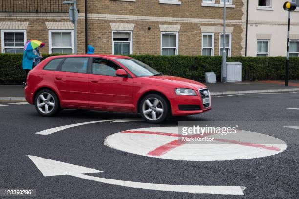 Red vehicle passes a mini-roundabout painted with the St George's flag on 10th July 2021 in Windsor, United Kingdom. The Royal Borough of Windsor and...