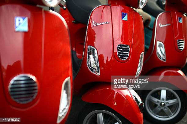 Red Vespa are parked in a street on December 9 2013 in Rome AFP PHOTO / GABRIEL BOUYS