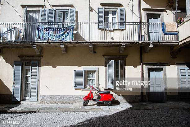 Red Vespa scooter, produced by Piaggio & C. SpA, stands parked outside a residential building in Pontida, Italy, on Monday, Oct. 3, 2016. After...