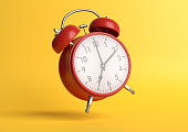 Red vintage alarm clock falling on the floor with bright yellow background in pastel colors