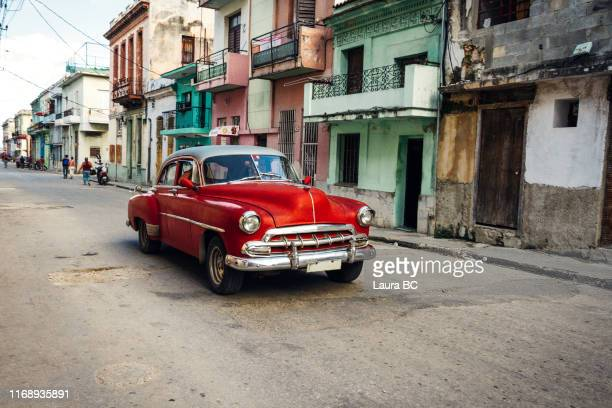 red vintage car driving in havana. - cuba stock pictures, royalty-free photos & images