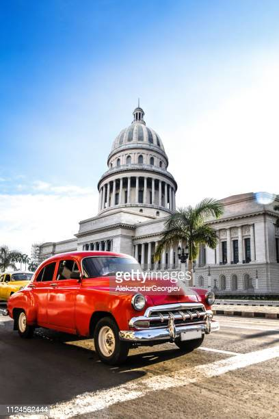 red vintage car in front el capitolio building in havana, cuba - cuba foto e immagini stock