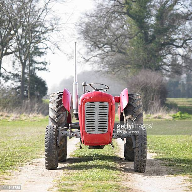 Red vintage tractor on track in countryside.