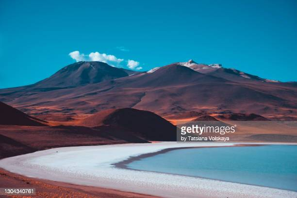 red volcanic mountains and a blue salt lake. beautiful nature background - scenics stock pictures, royalty-free photos & images