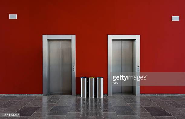 Red wall and two elevator doors