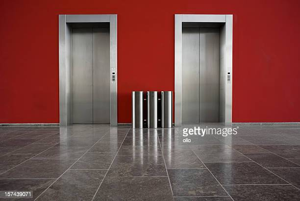 Red wall, two elevator doors, copy space