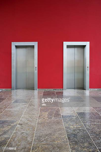 Red wall, two elevator doors, marble ground