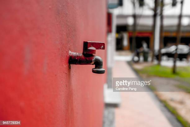 Red wall with a faucet.