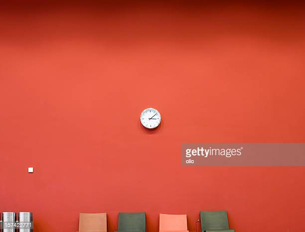 Red wall with clock and four seats