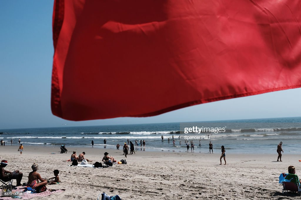A red warning flag flaps in the wind along Rockaway Beach as visitors try to stay cool on a hot summer day on August 22, 2017 in the Queens borough of New York City. New York and much of the Northeast is experiencing warm and muggy weather with temperatures in the 90's and a heat index of over 100.