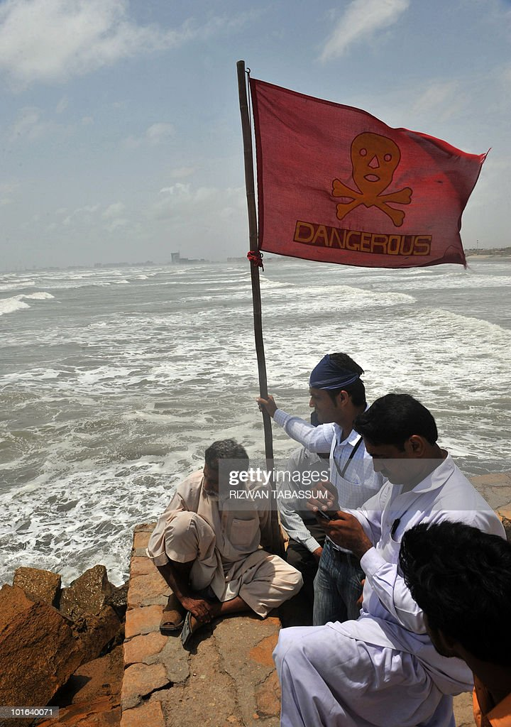 A red warning flag saying 'dangerous' adorned with skull and bones flies in the sea breeze as Pakistani men gather at the popular Seaview Beach in Karachi on June 5, 2010. Pakistan issued a danger warning on June 4 over Cyclone Phet, which may hit the coast packing winds of 120 kilometres an hour, as relief workers were on standby to evacuate residents forcibly if needed. AFP PHOTO/Rizwan TABASSUM
