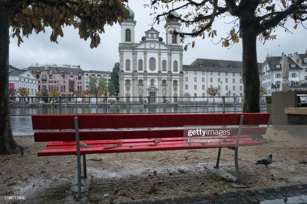 Red wet bench and Jesuit Church across Reuss river,Lucerne. : Stock Photo