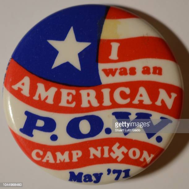Red white and blue antiwar pinback button or badge with a stylized American Flag background and the text 'I Was An American POW Camp Nixon May '71'...