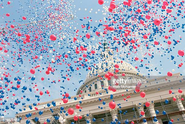 red, white, and blue balloons over the u.s. capitol building - politics stock pictures, royalty-free photos & images
