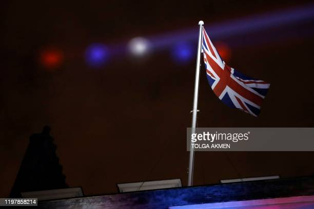 Red white and blue lights illuminate a Union flag flying atop 10 Downing Street the official residence of Britain's Prime Minister in central London...