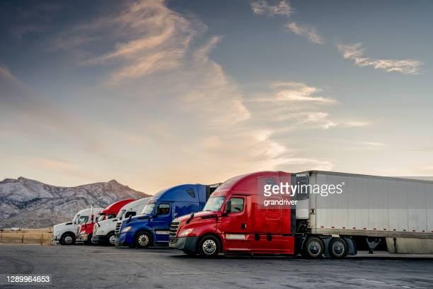 rot-weiß-blau geparkte lastwagen an einer lkw-haltestelle aufgereiht - konvoi stock-fotos und bilder