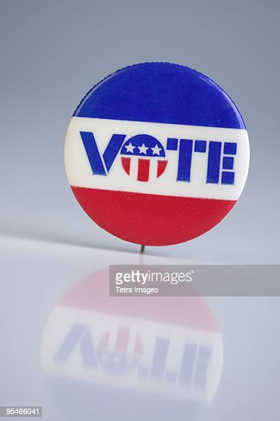 A red white and blue pin that says vote
