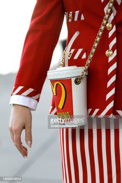 Red, white and yellow milkshake cup bag with gold details by Moschino x Jeremy Scott as a detail of spiritual healer Ira Wolff during a street style...