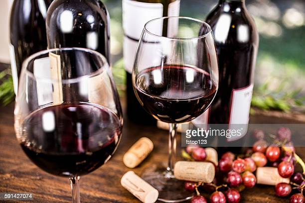 Red wine and grapes on outdoor dining table.